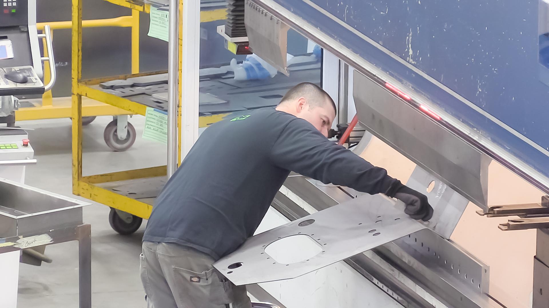 Worker Using Press Brake to Form Metal